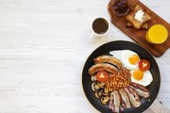 Full English breakfast in a pan with fried eggs, bacon, sausages, beans and toasts on white wooden background, top view. Copy spac. E. Flat lay. From above Stock Images
