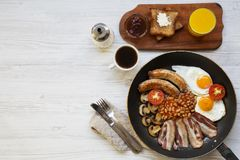 Full English breakfast in a pan with fried eggs, bacon, sausages, beans and toasts on white wooden background, top view. Copy spac. E. Flat lay. From above Stock Image
