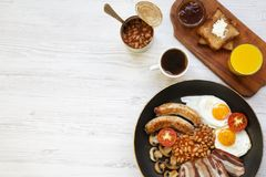 Full English breakfast in a pan with fried eggs, bacon, sausages, beans and toasts on white wooden background, top view. Copy spac. E. Flat lay. From above Royalty Free Stock Photos