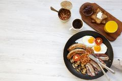Full English breakfast in a pan with fried eggs, bacon, sausages, beans and toasts on white wooden background, top view. Copy spac. E. Flat lay. From above Royalty Free Stock Image
