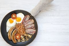 Full English Breakfast in pan with sausages, mushrooms, fried eggs, beans, tomato and bacon on a white wooden background. Copy spa. Ce. Top view. Flat lay. From Royalty Free Stock Photography