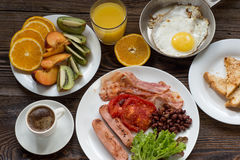 Full English breakfast with sausage, baked tomato, beans and toa Stock Photos
