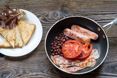 Full English breakfast with sausage, baked tomato, beans and toa Stock Image
