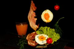 Full English breakfast with scrambled eggs, bacon, beans, tomatoes and orange juice. Black background. stock photography