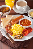 Full english breakfast with scrambled eggs, bacon, sausage, bean Royalty Free Stock Photo