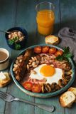 Full English breakfast with scrambled eggs, sausage, mushrooms, beans and bacon on a wooden rustic green table.Toast with butter, royalty free stock image