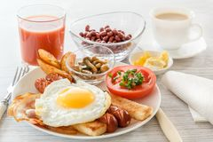 Full English breakfast with smoked sausages, fried egg, bacon, tomato, toast and beans. Tea with milk. A glass of fresh juice. Cut Stock Image