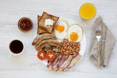 Full English Breakfast on a white round plate with fried eggs, bacon, sausages, beans and toasts on white wooden background, top v. Iew. Flat lay. From above Royalty Free Stock Images