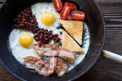 Full English cooked breakfast with bacon,  fried egg and toasts. Stock Image