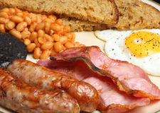 Full English Cooked Fried Breakfast. English cooked breakfast with sausages, bacon, baked beans, black pudding and fried bread Royalty Free Stock Image