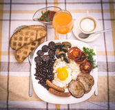 Full English fried breakfast with bacon, egg, sausages, black pudding, mushrooms Stock Photo
