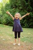 Full för höjd stående utomhus av den lyckliga Acive blonda flickan som skriker i parkera under sommardag arkivbild