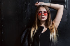 Full face portrait of fashion model in sunglasses with loose long fair hair posing in black surrounding.  Stock Photos