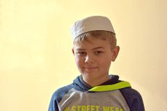Full face portrait image of young cute muslim boy wearing traditional islamic prayer hat cap. Young cute muslim boy wearing traditional islamic prayer hat cap Stock Images