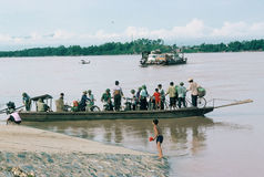 Full Ferry in Viet Nam. Crowded ferry with buses crossing a river in northern Vietnam, as a smaller ferry departs shore, also very crowded Stock Photography