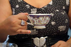 Full Figured Woman Having Tea. Time with black and white printed dress, big ring Royalty Free Stock Images