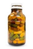 Full flaska av olika mångfärgade preventivpillerar Arkivfoton