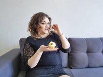 Full flicka för Beautifu cutel med pajer på soffanöjefrukosten arkivbild