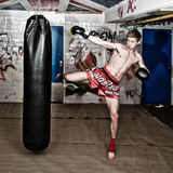 Full force kick. A muay thai fighter giving a high kick during a practice round with a boxing bag in an urban basement Royalty Free Stock Image