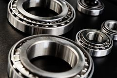 Collections of metal bearings. Full frame industrial background - metal bearings in close-up on a black background stock images
