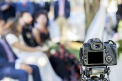 Full Frame reflex DSLR camera over tripod recording the wedding. Ceremony. Unidentified people Stock Photo