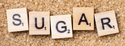 Full frame Word `sugar` on scrabble uppercase letters. Over a brown sugar surface royalty free stock image