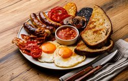 Full fry up English breakfast with fried eggs, sausages, bacon. Black pudding, beans and toasts on wooden background stock images