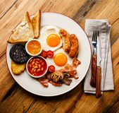 Full fry up English breakfast with fried eggs, sausages, bacon. Black pudding, beans and toasts on wooden background Stock Photo