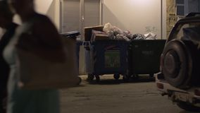 Full garbage containers in the street at night. NEA KALLIKRATIA, GREECE - AUGUST 12, 2017: People walking and cars driving in the street with full dumpsters stock footage