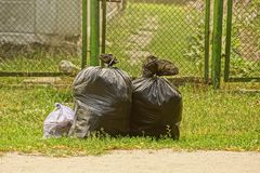 Full of garbage plastic bags on the lawn before the fence Stock Photos