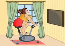 Full girl is engaged on a stationary bike at home Royalty Free Stock Image