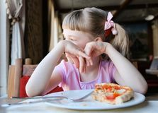 Full and glad child with a piece of a pizza stock images