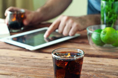 Full glass beaker of cola on a wooden table stock photography