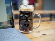 Full glass beer mug sitting next to laptop computer royalty free stock photography
