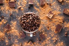Full glass cup of Roasted coffee beans on the dark stone background with dissipate cocoa, pieces of chocolate and beans. Selective Stock Images