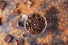 Full glass cup of Roasted coffee beans on the dark stone background with dissipate cocoa, pieces of chocolate and beans. Selective Stock Photo