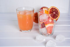 Full glass of grapefruit juice and glass of sliced fruit Stock Images