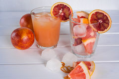 Full glass of grapefruit juice and glass of sliced fruit Royalty Free Stock Image