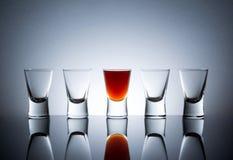 Full glass near empty glasses Royalty Free Stock Photos