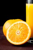 Full glass of orange juice near half orange with space for text Royalty Free Stock Photography