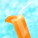 Full glass of orange juice with a slice of orange on a background of blue water Royalty Free Stock Image