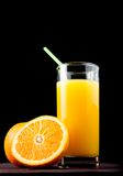 Full glass of orange juice with straw near half orange Stock Photo