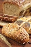 Full grain bread roll on wooden table with ear of rye Royalty Free Stock Image