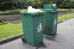 Full green garbage bin on road. In park Royalty Free Stock Image