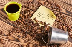 Full green metal bucket of black coffee and empty zinked bucket near paper sticker with inscription boss and scattered lot of roas. Ted beans on old worn wooden stock photo