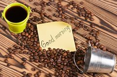 Full green metal bucket of black coffee and empty zinked bucket near paper sticker with inscription good morning and scattered lot. Of roasted beans on old worn royalty free stock images