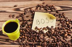 Full green metal bucket of black coffee and empty zinked bucket near paper sticker with inscription boss and scattered lot of roas. Ted beans on old worn wooden royalty free stock photo