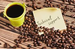 Full green metal bucket of black coffee and empty zinked bucket near paper sticker with inscription technical support and scattere. D lot of roasted beans on old stock photos