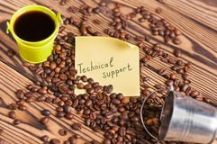 Full green metal bucket of black coffee and empty zinked bucket near paper sticker with inscription technical support and scattere. D lot of roasted beans on old royalty free stock image