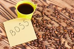 Full green metal bucket of black coffee near paper sticker with inscription boss and scattered lot of roasted beans. On old worn wooden table royalty free stock photography